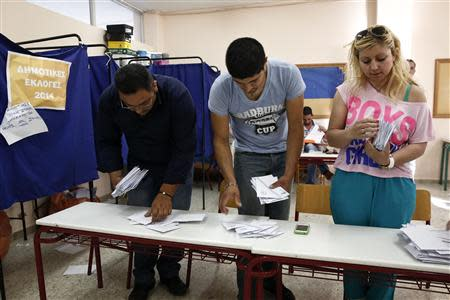 Members of an electoral commission sort ballots into stacks before counting them after the end of voting at a polling station in Hellenikon, a southern suburb of Athens May 18, 2014. REUTERS/Yorgos Karahalis