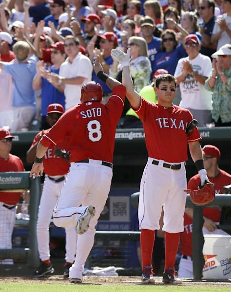 Texas Rangers' Geovany Soto (8) is congratulated by Ian Kinsler, right, at the dugout entrance after Soto scored on a Craig Gentry single in the fifth inning of a baseball game against the Los Angeles Angels, Sunday, Sept. 29, 2013, in Arlington, Texas. The Rangers' A.J. Pierzynski also scored on the single by Gentry. (AP Photo/Tony Gutierrez)