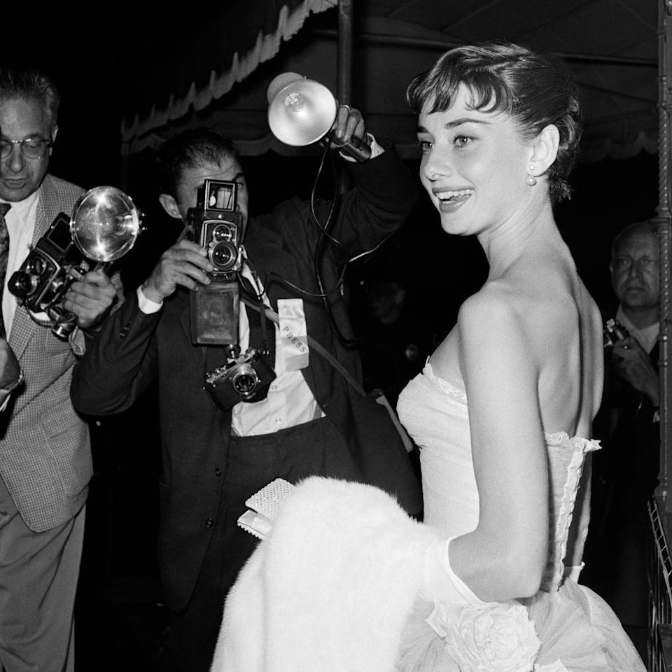 <p>Audrey Hepburn received her breakout role in <em>Roman Holiday </em>in 1953—and here she is posing for cameras at the premiere. The actress went on the star in several more iconic films, including <em>Breakfast at Tiffany's</em> and <em>Sabrina. </em></p>
