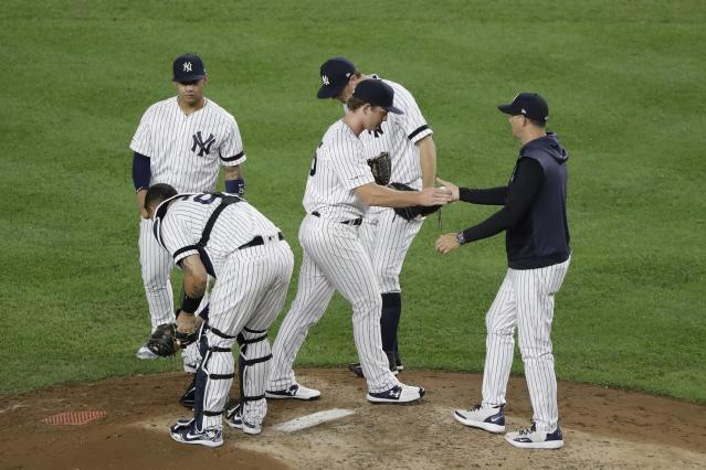New York Yankees pitcher Chance Adams hands the ball to manager Aaron Boone as he leaves during the seventh inning of the team's baseball game against the Cleveland Indians on Thursday, Aug. 15, 2019, in New York. (AP Photo/Frank Franklin II)