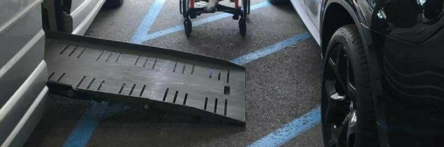 Image of a handicap accessible van with the ramp out with a car parked on the stripped loading area. A oung child sits between the cars showing it is impossible for him to access the ramp into his vehicle because of the car blocking access to the ramp