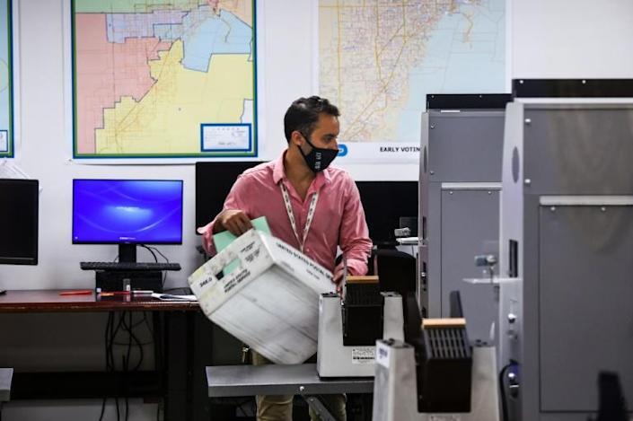 An electoral worker helps with the vote-by-mail ballot scanning process at the Miami-Dade County Election Department on October 21, 2020