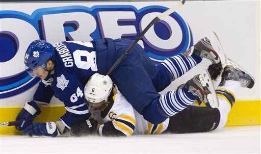 Toronto Maple Leafs forward Mikhail Grabovski, top, collides on top of Boston Bruins defenseman Greg Zanon, bottom, during second period NHL hockey action in Toronto on Tuesday, March. 6, 2012. (AP Photo/The Canadian Press, Nathan Denette)