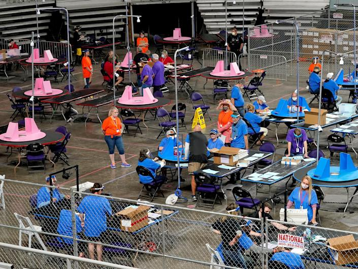 In this May 6, 2021, file photo, Maricopa County ballots cast in the 2020 general election are examined and recounted by contractors working for Florida-based company, Cyber Ninjas at Veterans Memorial Coliseum in Phoenix.
