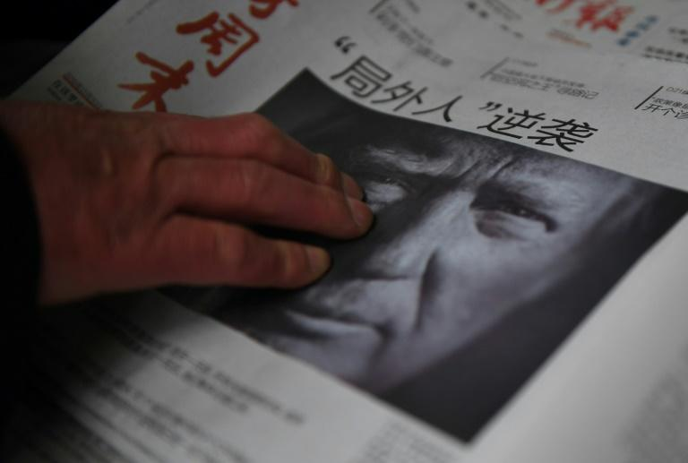 A man buys a newspaper featuring a photo of US President-elect Donald Trump in Beijing