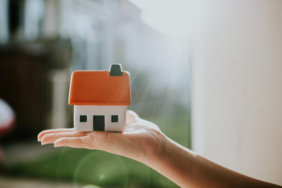 Hand holding a little house with an orange roof. Conceptual image with space for copy.