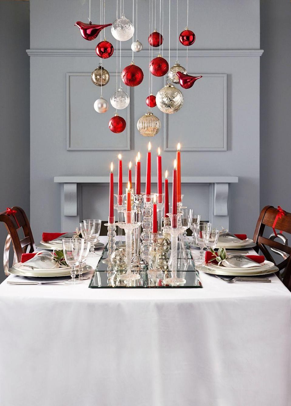 """<p>Along with suspending ornaments above your dining table, illuminate your space with an arrangement of tall red candlesticks. It's an easy way to give dinner guests a warm welcome and make your dining room more welcoming.</p><p><a class=""""link rapid-noclick-resp"""" href=""""https://www.amazon.com/CandleNScent-Taper-Candles-Tapered-Candlesticks/dp/B07VYV6FNY/ref=asc_df_B07VYV6FNY/?tag=syn-yahoo-20&ascsubtag=%5Bartid%7C10055.g.2196%5Bsrc%7Cyahoo-us"""" rel=""""nofollow noopener"""" target=""""_blank"""" data-ylk=""""slk:SHOP RED CANDLESTICKS"""">SHOP RED CANDLESTICKS</a></p>"""