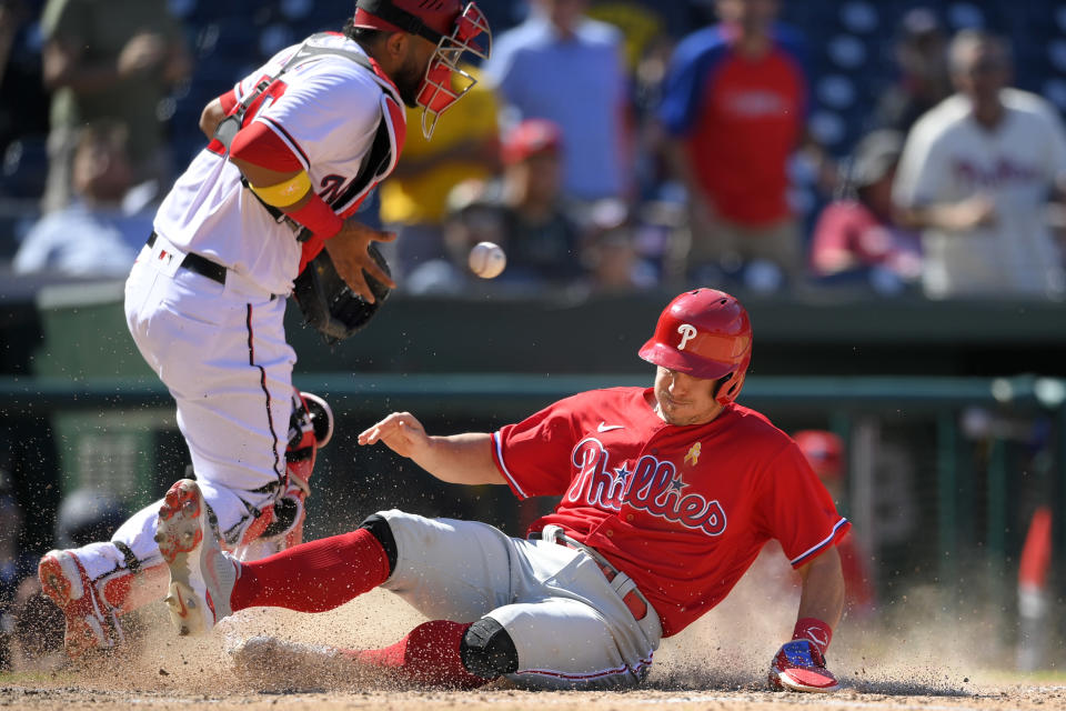 Philadelphia Phillies' J.T. Realmuto, right, slides home to score on a double by Andrew McCutchen as Washington Nationals catcher Keibert Ruiz, left, fields the late throw during the sixth inning of a baseball game, Thursday, Sept. 2, 2021, in Washington. The Phillies won 7-6. (AP Photo/Nick Wass)