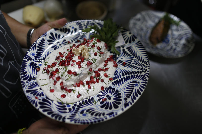 In this Sept. 13, 2019 photo, a cook carries out finished chiles en nogada to be served to diners at Testal restaurant in downtown Mexico City. Testal has dedicated nearly an entire kitchen to the production of the emblematic dish, selling around 150 chiles per day, and attempting to more than double the 3000 chiles they sold last year during the short season. (AP Photo/Rebecca Blackwell)
