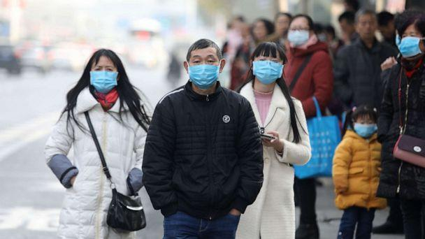 PHOTO: Chinese residents wear masks near the closed Huanan Seafood Wholesale Market, which has been linked to cases of a new strain of Coronavirus identified as the cause of the pneumonia outbreak in Wuhan, Hubei province, China, Jan. 20, 2020. (STR/EPA via Shutterstock)