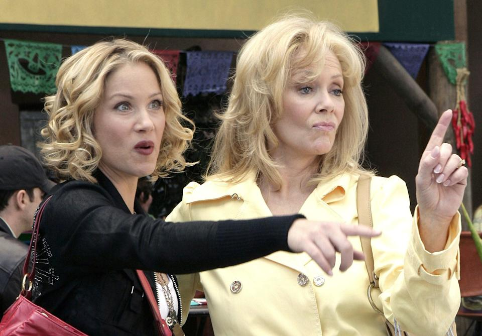 Two blonde women with their fingers raised talking to someone offscreen