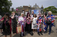 Royal fans share a toast as they stand in front of the gates of Kensington Palace in London, Thursday, July 1, 2021, to mark what would have been Princess Diana's 60th birthday. Princes William and Harry are due on Thursday to unveil a statue of their mother, Princess Diana, on what would have been her 60th birthday. The event in the Sunken Garden at London's Kensington Palace will be their second public meeting since Harry and Meghan stepped away from royal duties over a year ago. (AP Photo/Frank Augstein)
