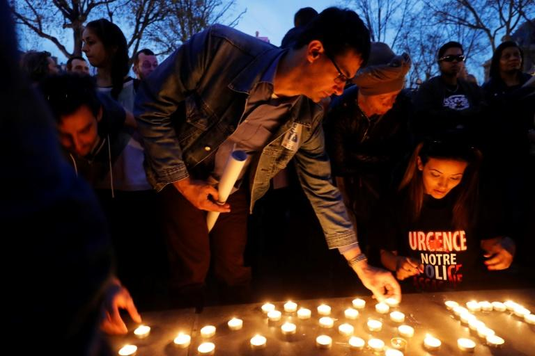 Demonstrators light candles during a protest in Paris over  the death of Chinese Liu Shaoyo, shot dead by French police