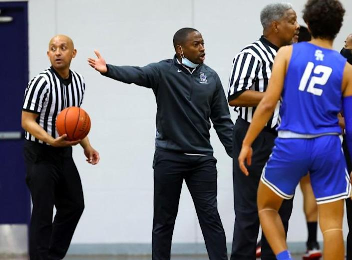 Santa Margarita basketball coach Justin Williams-Bell, center, reacts from the sideline during a game.