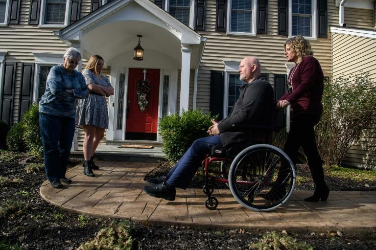 Katie Marcoux (R) pushes her husband Eric in his wheelchair as her mother Judy Christensen (L) and her daughter Eva Kolb (2nd L) look on in Potomac, Maryland, on December 3, 2020