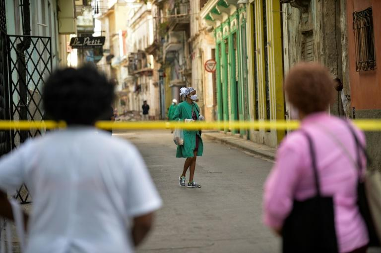 Covid-19 support personnel walk along a cordoned-off street after cases of coronavirus were detected in Havana. Cuban authorities announced new measures to control a surge of COVID-19 with increased penalties for people who do not comply