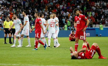 Soccer Football - World Cup - Group B - Iran vs Spain - Kazan Arena, Kazan, Russia - June 20, 2018 Iran players look dejected after the match as Spain players celebrate REUTERS/Toru Hanai