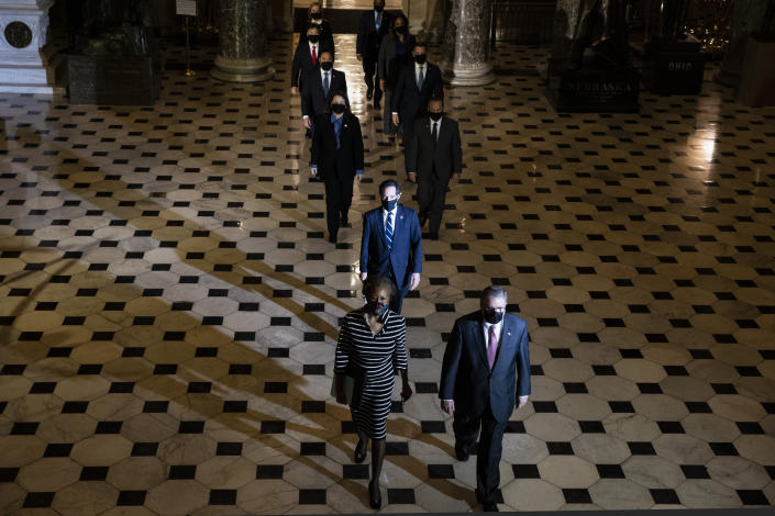 Clerk of the House Cheryl Johnson along with acting House Sergeant-at-Arms Tim Blodgett, right, and Rep. Jamie Raskin, D-Md., lead the Democratic House impeachment managers as they walk through Statuary Hall on Capitol Hill to deliver to the Senate the article of impeachment alleging incitement of insurrection against former President Donald Trump, in Washington, Monday, Jan. 25, 2021. (Tasos Katopodis/Pool Photo via AP)