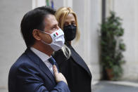 FILE - In this Saturday, Feb. 13, 2021 file photo, Italy's outgoing Premier, Giuseppe Conte and his partner Olivia Paladino pose and acknowledge the applause of the employees of Chigi Palace Premier's office in Rome. When Giuseppe Conte exited the premier's office, palace employees warmly applauded in him appreciation. But that's hardly likely to be Conte's last hurrah in politics. Just a few hours after the handover-ceremony to transfer power to Mario Draghi, the former European Central Bank chief now tasked with leading Italy in the pandemic, Conte dashed off a thank-you note to citizens that sounded more like an ''arrivederci″ (see you again) then a retreat from the political world he was unexpectedly propelled into in 2018.(Alberto Pizzoli/Pool via AP, File)