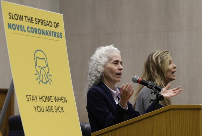 FILE - In this March 12, 2020, file photo, Los Angeles County Public Health Director Barbara Ferrer, left, takes questions at a news conference in Los Angeles. At right is Niago Wilson, a sign language interpreter. California officials are blaming a backlog in Los Angeles County for a sudden doubling in positive coronavirus cases and uptick in the state's positivity rate last week, but said lower numbers released Monday, Oct. 26, 2020, are accurate. (AP Photo/Damian Dovarganes, File)