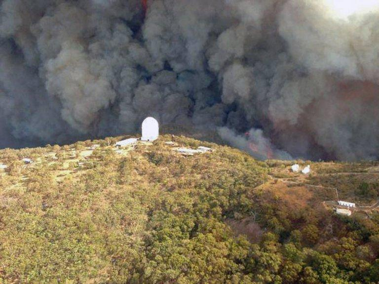 Photo taken on January 13, 2013 shows smoke billowing from a fire near the Siding Spring Observatory