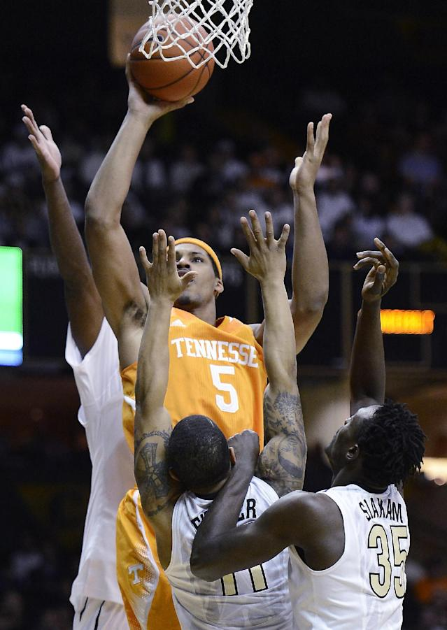 Tennessee forward Jarnell Stokes (5) goes to the basket against Vanderbilt guard Kyle Fuller (11) and forward James Siakam (35) in the first half of an NCAA college basketball game, Wednesday, Feb. 5, 2014, in Nashville, Tenn. (AP Photo/Mark Zaleski)