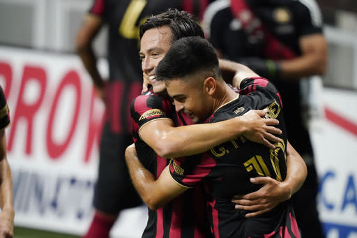 Atlanta United midfielder Gonzalo Martinez, right, hugs forward Erick Torres after Martinez scored during the second half of an MLS soccer match against Nashville SC on Saturday, Aug. 22, 2020, in Atlanta. (AP Photo/Brynn Anderson)