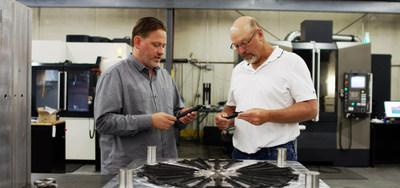 Allegiance Mold President and CEO Ted Stender and senior mold designer Dave VanDeLaare inspecting final parts from plastic injection mold designed and manufactured using Cimatron