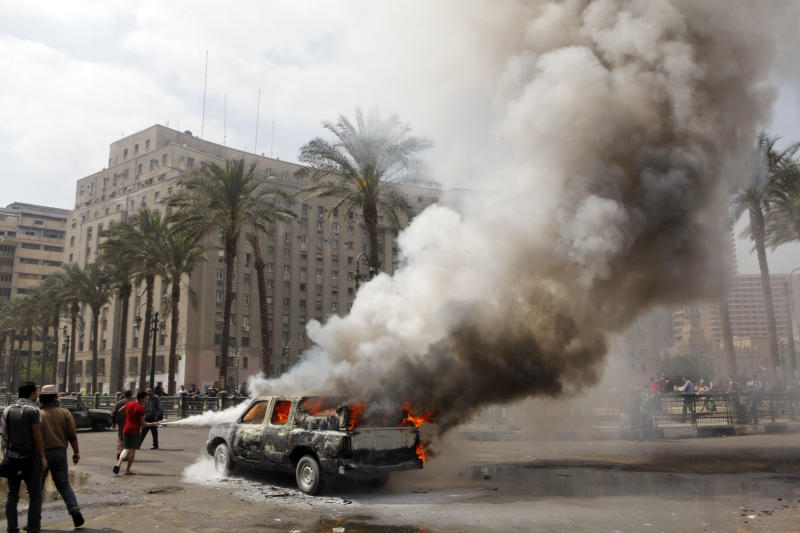 Egyptians extinguish a burning police vehicle, which has been set afire by angry protesters in Tahrir Square, once the epicenter of protests against former President Mubarak, in Cairo, Egypt, Monday, March 18, 2013. Egypt is currently mired in another wave of protests, clashes and unrest that have plagued the country since the ouster of authoritarian leader Hosni Mubarak in the pro-democracy uprising two years ago. (AP Photo/Amr Nabil)