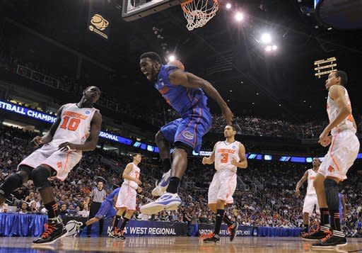 Florida's Patric Young, center, celebrates a dunk as Louisville's Gorgui Dieng (10), Peyton Siva (3) and Jared Swopshire, right, watch during the first half of an NCAA tournament West Regional final college basketball game, Saturday, March 24, 2012, in Phoenix. (AP Photo/Chris Carlson)