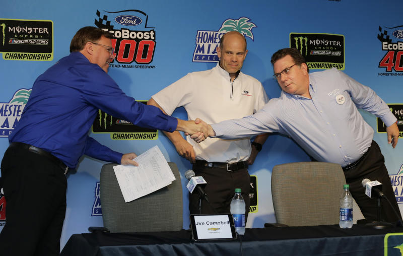 Manufacturers representatives, from left, Jim Campbell for Chevrolet, Mark Rushbrook for Ford, and Ed Laukes for Toyota, shake hands after a press conference before practice for a NASCAR Cup Series auto race on Saturday, Nov. 16, 2019, at Homestead-Miami Speedway in Homestead, Fla. (AP Photo/Terry Renna)