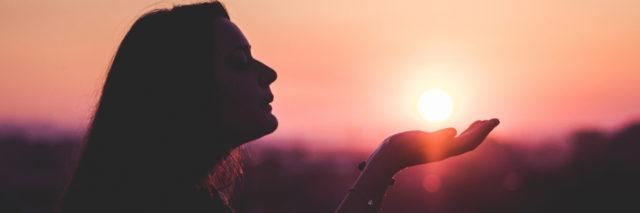 A woman with her hand out at sunset.