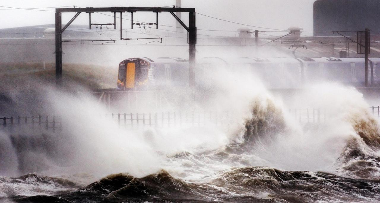 A train makes its way through strong winds as high waves batter the shore near Saltcoats, North Ayrshire, Scotland, as the remnants of Hurricane Katia hit British shores, Monday Sept. 12, 2011. Britain's weather agency says the tail end of former Hurricane Katia could bring the worst storms to hit the country in 15 years. Britain's Met Office said post Tropical Storm Katia was hitting parts of Northern Ireland, North Wales, Northern England and parts of Scotland on Monday. It said the storms could be the worst to hit Britain since 1996 when the aftermath of Hurricane Lili brought winds of 90 mph (145 kph) to the country. (AP Photo/PA, Danny Lawson) UNITED KINGDOM OUT NO SALES NO ARCHIVE