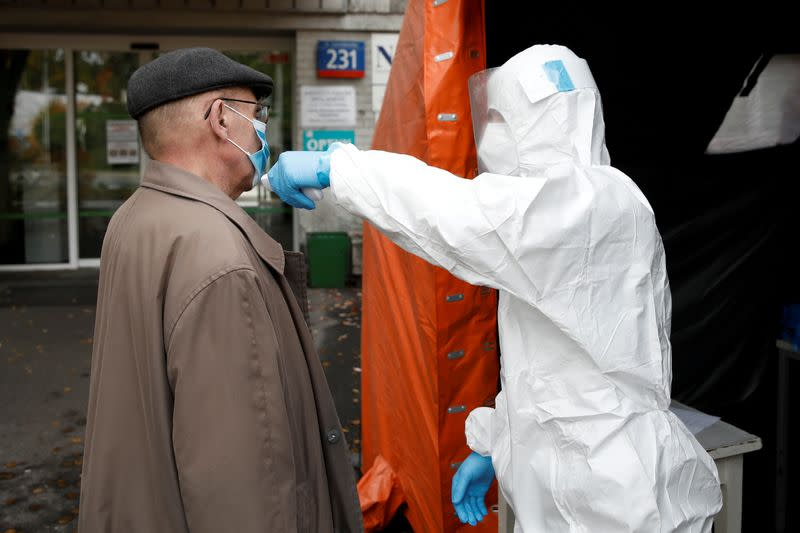 FILE PHOTO: A man in protective suit checks a man's temperature in Warsaw