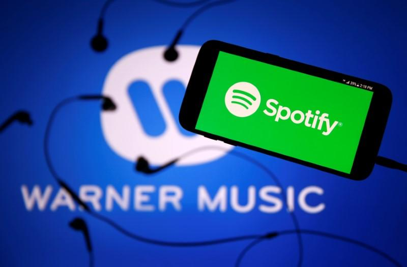 A smartphone with a headset with Spotify logo are seen in front of a displayed Warner Music logo in this illustration picture