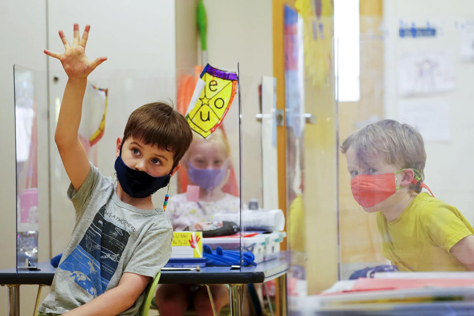 FILE - In this May 18, 2021, file photo, kindergarten students wear masks and are separated by plexiglass during a math lesson at the Milton Elementary School, in Rye, N.Y. School districts across the United States are hiring additional teachers in anticipation of what will be one of the largest kindergarten classes ever as enrollment rebounds following the pandemic. (AP Photo/Mary Altaffer, File)