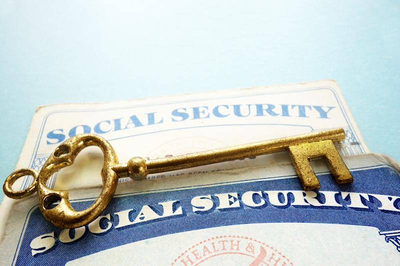 A gold key lying atop two Social Security cards.