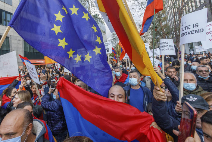 Protestors wave EU flags and hold signs outside of an EU summit meeting in Brussels to demonstrate in support of Armenia and against the war in the Nagorno-Karabakh region, Thursday, Oct. 1, 2020. The mountainous region of Nagorno-Karabakh, where deadly new fighting has erupted in recent days between Armenian and Azerbaijani military forces, has been in a tense limbo since a 1994 truce. (AP Photo/Olivier Matthys)