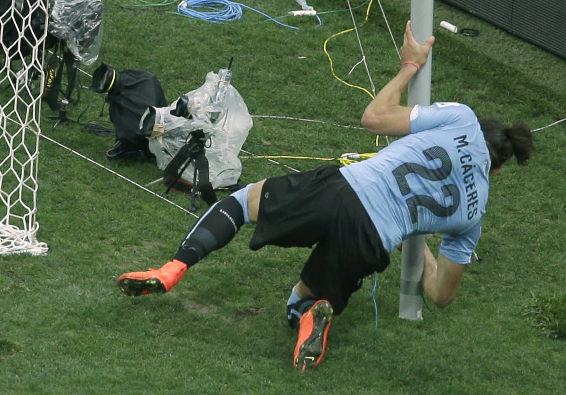 Uruguay's Martin Caceres collides with a post holding the goal net during the group D World Cup soccer match between Uruguay and England at the Itaquerao Stadium in Sao Paulo, Brazil, Thursday, June 19, 2014.  (AP Photo/Michael Sohn)