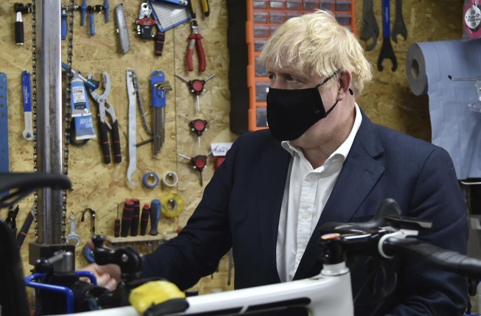 Britain's Prime Minister Boris Johnson talks to the owner of the the Cycle Lounge, Rodney Rouse, a bicycle repair shop Beeston near Nottingham, England, Tuesday, July 28, 2020. The government is launching a new cycling intuitive to help get people fitter. (AP Photo/Rui Vieira, Pool)