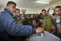 """FILE - In this Jan. 9, 2005 file photo, Zakaria Zubeidi, then West Bank leader of Palestinian militant group Al Aqsa Martyrs Brigades votes during the Palestinian election, in the West Bank town of Jenin. For nearly two decades, Zubeidi has been an object of fascination for Israelis and Palestinians alike, who have seen his progression from a child actor to a swaggering militant, to the scarred face of a West Bank theater promoting """"cultural resistance"""" to Israeli occupation. In his latest act, he has emerged as one of Israel's most wanted fugitives after tunneling out of a high-security prison on Monday, Sept. 6, 2021 with five other Palestinian militants. (AP Photo/Brennan Linsley)"""