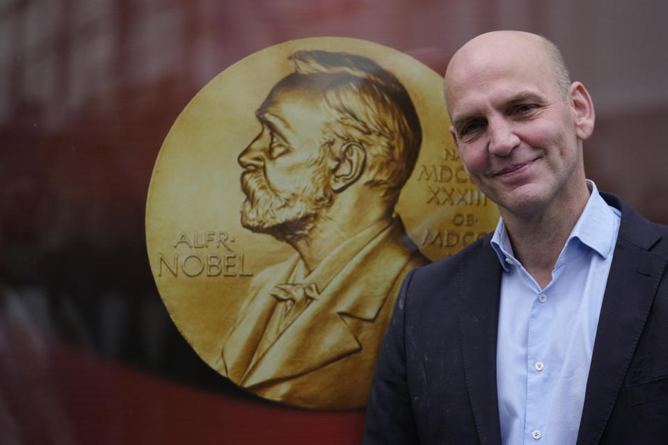 """German scientist Benjamin List poses next to a poster with a medal of Alfred Nobel as arrives at the Max-Planck-Institute for Coal Research in Muelheim, Germany, Wednesday, Oct. 6, 2021. Two scientists have won the Nobel Prize for chemistry for finding an """"ingenious"""" new way to build molecules that can be used to make everything from medicines to food flavorings. Benjamin List of Germany and Scotland-born David W.C. MacMillan developed """"asymmetric organocatalysis."""" (AP Photo/Martin Meissner)"""