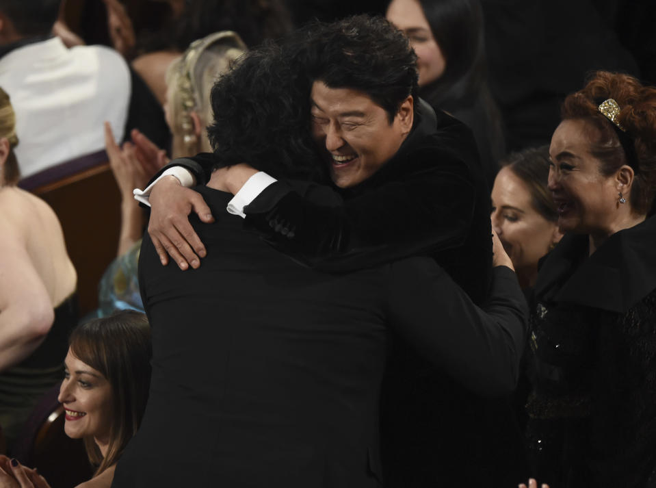 "Bong Joon Ho, left, is congratulated by Kang-Ho Song before going on stage to accept the award for best international feature film for ""Parasite,"" from South Korea, at the Oscars on Sunday, Feb. 9, 2020, at the Dolby Theatre in Los Angeles. (AP Photo/Chris Pizzello)"