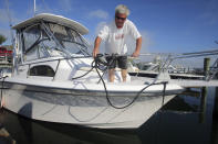 Rob Edwards, from Newport, R.I., adds extra lines to secure his boat at the Goat Island Marina, Saturday, Aug. 21, 2021, in Newport, R.I. New Englanders, bracing for their first direct hit by a hurricane in 30 years, are taking precautions as Tropical Storm Henri barrels toward the southern New England coast. (AP Photo/Stew Milne)