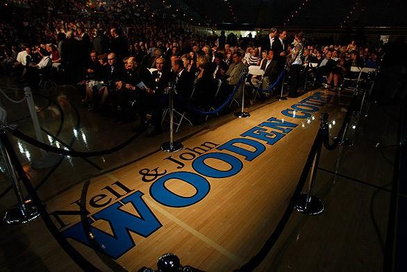"""A spotlight shines on the new name for the Pauley Pavilion basketball court at UCLA during the memorial service for the legendary coach. His wife, Nell, is recognized for her role in a partnership that remained solid through 27 years of basketball coaching. <span class=""""copyright"""">(Allen J. Schaben / Los Angeles Times)</span>"""
