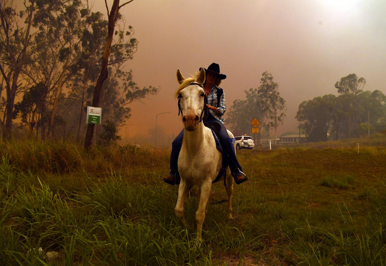 <p>Rhonda Anderson evacuates herself and her horse to safety near Mount Larcom. Source: AAP </p>