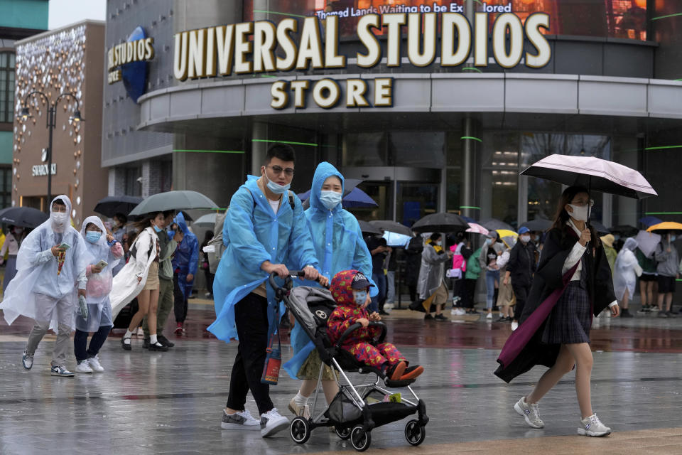 A family wearing raincoats and face masks to help protect from the coronavirus walk by masked visitors lining up to enter a Universal Studios store as they visit Universal Studios Beijing in Beijing, Monday, Sept. 20, 2021. Thousands of people brave the rain visit to the newest location of the global brand of theme parks which officially opens on Monday. (AP Photo/Andy Wong)