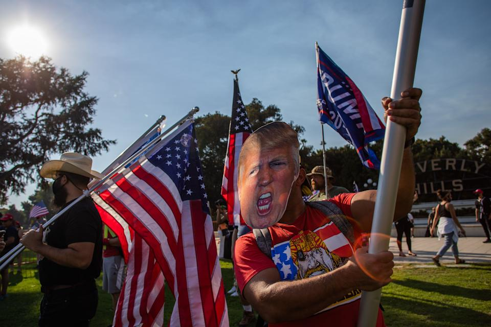 A man wearing a mask of US President Donald Trump holds a US flag during a pro-Trump rally in Beverly Hills, California on October 3, 2020. (Photo by Apu GOMES / AFP) (Photo by APU GOMES/AFP via Getty Images)