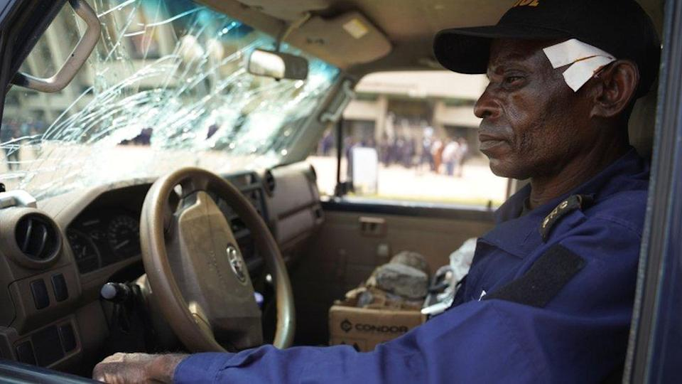 A wounded policeman, Nsonso Lenga Lambert, sits in a police vehicle that was damaged when two groups of Muslims clashed outside Martyrs' Stadium in Kinshasa, Democratic Republic of Congo - 13 May 2021.
