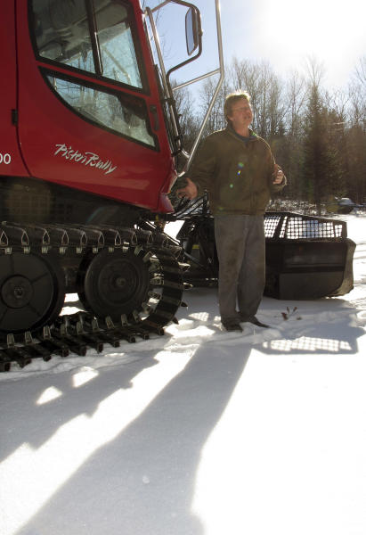 Barre Sno-Bees Snowmobile Club Trailmaster Tim Stone stands in front of the tractor the club uses to pull trail grooming equipment, Wednesday, Jan. 22, 2014, in Barre, Vt. Below-zero temperatures are being reported across Vermont but unlike most of New England and parts of the mid-Atlantic, heavy snow continues to evade the state. (AP Photo/Wilson Ring)